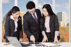 Multiracial workers discussing with touchscreen tablet Royalty Free Stock Images