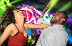 Multiracial young couple dancing at night club with laser light show. Happy people having crazy fun at nightclub after party - Nightlife drunk concept with royalty free stock images