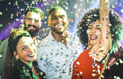 Multiracial young friends dancing at party night club. Multiracial young friends dancing at night club under confetti rain - Happy people having crazy fun at royalty free stock photo