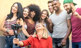 Multiracial young friends taking selfie with mobile smart phone and stabilizer gimbal - Friendship concept with millenial people stock photos