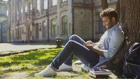 Multiracial young man sitting under tree, scrolling mobile phone screen, smiling Stock Photos