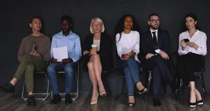 Multiracial applicants businesspeople sit on chairs prepare for job interview