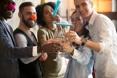 Multiracial young people clinking glasses blowing whistles celeb royalty free stock image