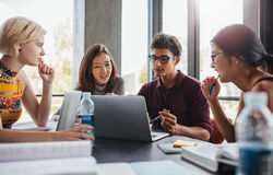 Multiracial young people doing group study at library. Multiracial young people doing group study at table. University students sitting together at table with Stock Photos