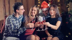 Attractive young friends celebrating xmas, new year or birthday party indoors. Multiracial young people wearing funny hats holding sparklers clinking glasses stock video