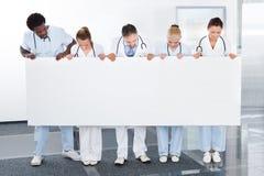 Multiraciale artsen die aanplakbiljet houden Stock Afbeelding