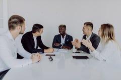 Multiraciale bedrijfsmensen die zitting toejuichen bij conferentielijst, divers team die handen na groepsvergadering slaan multin royalty-vrije stock foto's