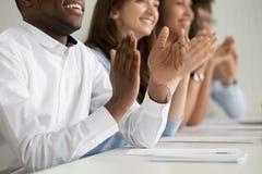 Multiraciale bedrijfspublieksmensen die zitting toejuichen bij conferentielijst, close-up royalty-vrije stock afbeelding