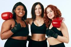 Multiraciale diverse vrouw drie in het zwarte sportkleding stellen in bokshandschoenen royalty-vrije stock fotografie