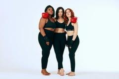 Multiraciale diverse vrouw drie in het zwarte sportkleding stellen in bokshandschoenen royalty-vrije stock foto's