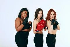 Multiraciale diverse vrouw drie in het zwarte sportkleding stellen in bokshandschoenen royalty-vrije stock afbeeldingen