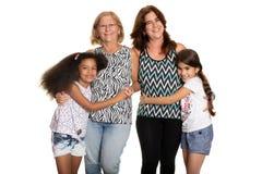 Multiraciale familie - Mamma en grootmoeder die hun gemengde gerende kinderen koesteren stock foto