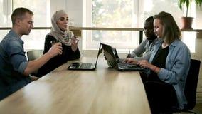 Multiraciale groep bedrijfsmensen die in modern helder bureau samenkomen Jong team die over vooruitgang van project bespreken stock video