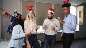 Multiraciale groep gelukkige beambten die glazen met mousserende wijn houden en sprekend etend snacks tijdens Kerstmis stock footage