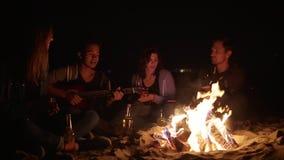 Multiraciale groep jonge jongens en meisjes die door het vuur laat bij nacht en het zingen liederen en het spelen gitaar zitten stock video