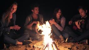 Multiraciale groep jonge vrouwen en mannen die door het vuur laat bij nacht en het zingen liederen, het spelen gitaar zitten en stock footage