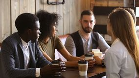 Multiraciale groep vrienden die koffie samen in comfortabele koffie drinken stock videobeelden