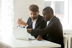 Multiraciale partners die in kostuums online project bespreken stock afbeelding