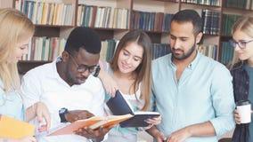 Multiraciale studenten die pret in bibliotheek hebben terwijl het voorbereidingen treffen voor examens stock videobeelden