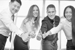Multiraciale succesvolle bedrijfsmensen met duimen op gebaar Stock Foto