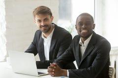 Multiraciale teamportret, Afrikaanse en Kaukasische partners lookin royalty-vrije stock afbeelding