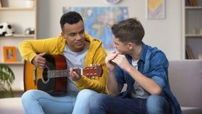 Multiraciale tienervrienden die gitaar en de mouthorgan carrière van de hobbymusicus spelen stock video
