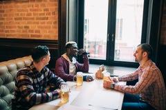 Multiraciale vrienden die en bier spreken drinken en glazen clinking bij bar royalty-vrije stock afbeelding
