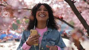 Multiraciale vrouw die aan muziek in een park bij de lente luisteren stock videobeelden