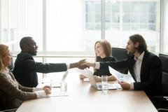 Multiraciale zakenlieden in kostuumshandenschudden bij uitvoerend team o royalty-vrije stock afbeeldingen