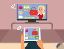 Multiscreen interaction. Woman is purchasing red. Bag online in TV shop using tablet pc Contains EPS10 and high-resolution JPEG Stock Photography