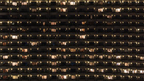 Multistorey block of flats at night. Facade of highrise apartment block with balconies. Electric lights in some windows. Housing in Bangkok, Thailand Stock Images