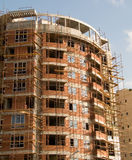 Multistorey housing. Red brick multistorey housing in scaffolding Royalty Free Stock Photo