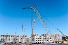 Multistorey housing under construction and construction cranes stock images