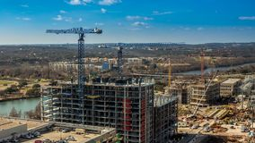 Multistoried skyscraper under construction with mechanic cranes in 4k time lapse. Multistoried skyscraper under construction with mechanic cranes in time lapse stock video footage
