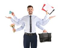 Multitask businessman with many hands holding different stuff on white background. Combining life and work stock photography