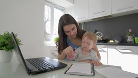 Multitasking материнство, ребенок воспитания комбайна дела женский и работа на ноутбуке и говорить на черни акции видеоматериалы