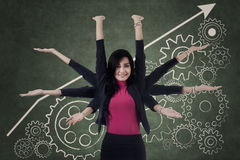 Multitasking businesswoman with cogwheel Stock Image