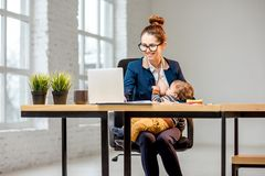 Multitasking businesswoman with her son working at the office stock photos