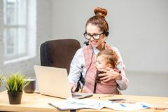 Businesswoman working with her baby son at the office Royalty Free Stock Photography