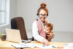 Businesswoman working with her baby son at the office Royalty Free Stock Images