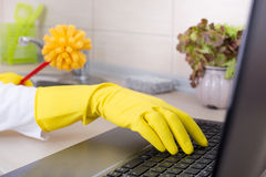 Multitasking concept. Woman with cleaning brush and laptop Royalty Free Stock Image