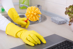 Multitasking concept. Woman with cleaning brush and laptop Stock Images
