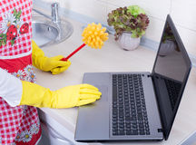 Multitasking concept. Woman with cleaning brush and laptop Royalty Free Stock Images