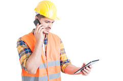 Multitasking concept with young constructor holding a tablet and Stock Photography