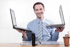 Multitasking employee with 2 laptops smiling Royalty Free Stock Photo