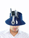 Multitasking Guy. An Asian guy wearing a hat brimming with different gadgets like a cellphone,watch and other things, depicting a multitasking mind Royalty Free Stock Images