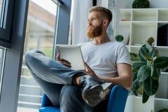 multitasking Hübsche tragende Gläser des jungen Mannes und Arbeiten mit Berührungsfläche beim Sitzen auf der Couch im Büro Lizenzfreies Stockfoto