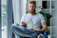 multitasking Hübsche tragende Gläser des jungen Mannes und Arbeiten mit Berührungsfläche beim Sitzen auf der Couch im Büro Lizenzfreie Stockfotos