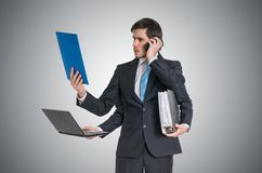 Multitasking man at work is calling with phone, reading report, working with laptop and holding office documents