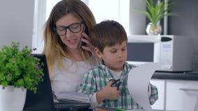 Multitasking moeder, vrouw met kind in wapens die op telefoon spreken en in notitieboekje schrijven stock videobeelden